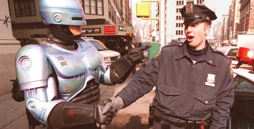 Aktor przebrany za Robocopa ściska rękę oficera policji na służbie. /AFP