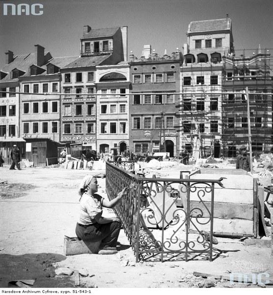 Odbudowa Starego Miasta w Warszawie. Prace wykończeniowe na Rynku Starego Miasta. Widoczna kobieta malująca metalową balustradę. Na dalszym planie widoczne kamienice na stronie Dekerta, 1953