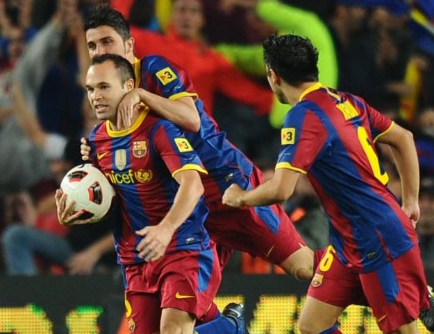 Andres Iniesta (z piłką) oraz Xavi (tyłem) znaleźli się w 11-tce kolejki Primera Division /AFP