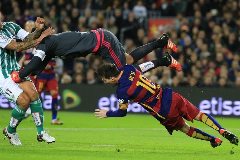 Antonio Adan wybija piłkę, a Lionel Messi upada /AFP