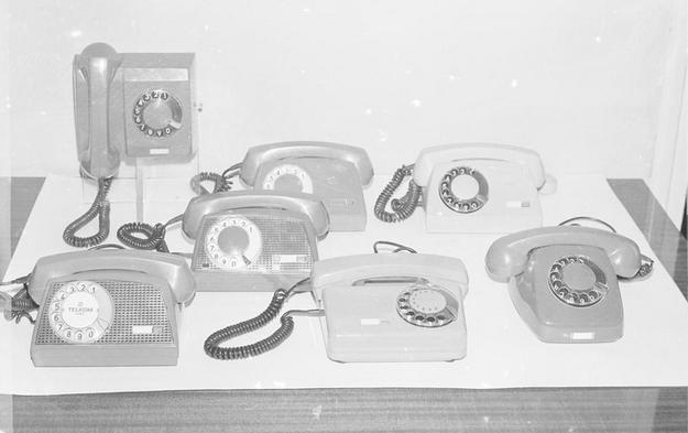 Aparaty telefoniczne. W pierwszym szeregu od lewej: Storczyk, Tulipan, Jaskier. W drugim szeregu Storczyk. W trzecim szeregu od prawej dwa aparaty Aster. Z tyłu jedyny wiszący aparat Irys (1976) /Z archiwum Narodowego Archiwum Cyfrowego