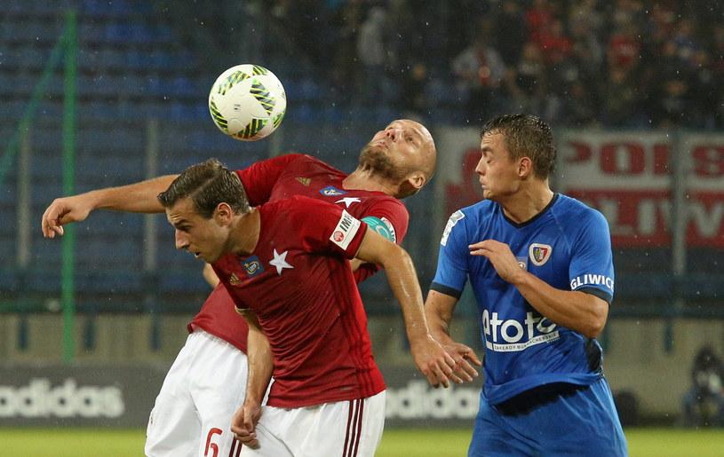 Arkadiusz Głowacki i Boban Jović walczą o piłkę z Michałem Masłowskim /Stanisław Rozpędzik /PAP