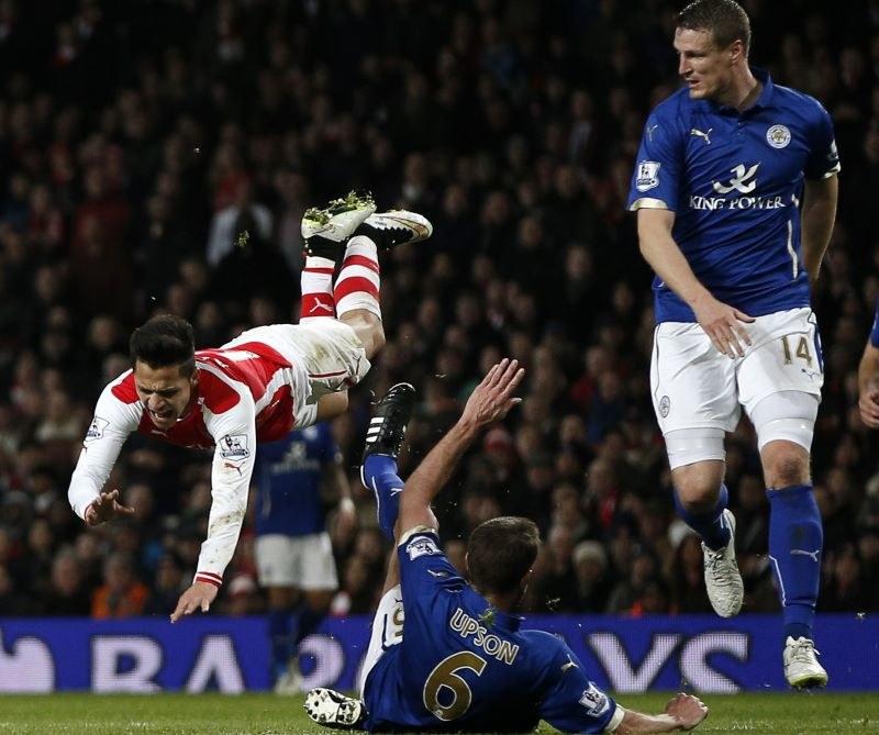 As Arsenalu Alexis Sanchez (w locie) po starciu z piłkarzem Leicesteru Matthew Upsonem /AFP