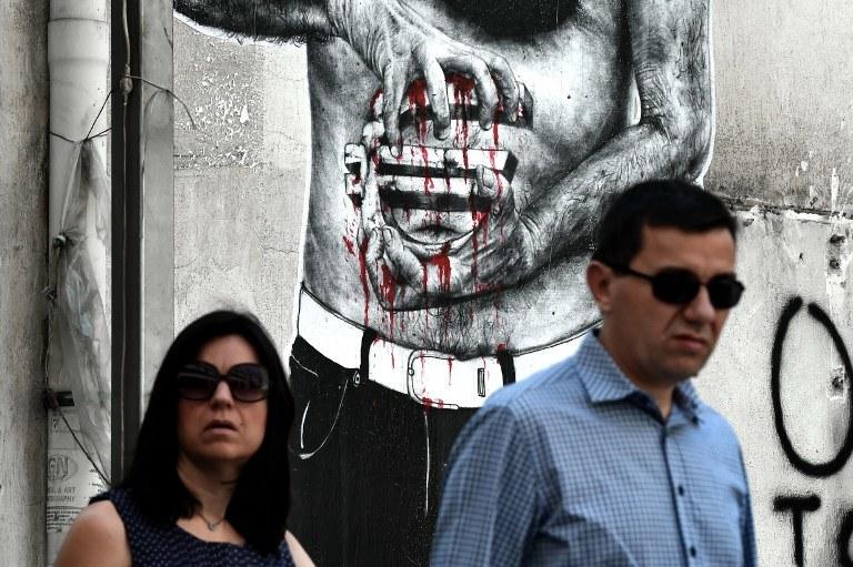 """Ateny: Graffitti przedstawiające """"krwawiące""""euro; zdj. ilustracyjne /ARIS MESSINIS / AFP /AFP"""