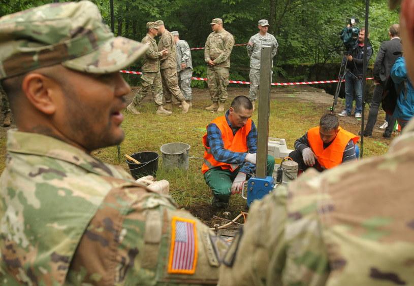 Badacze wykonują odwiert w stropie bunkra, pracom przyglądają się żołnierze amerykańscy, którzy przyjechali zwiedzić kompleks /Tomasz Waszczuk /PAP