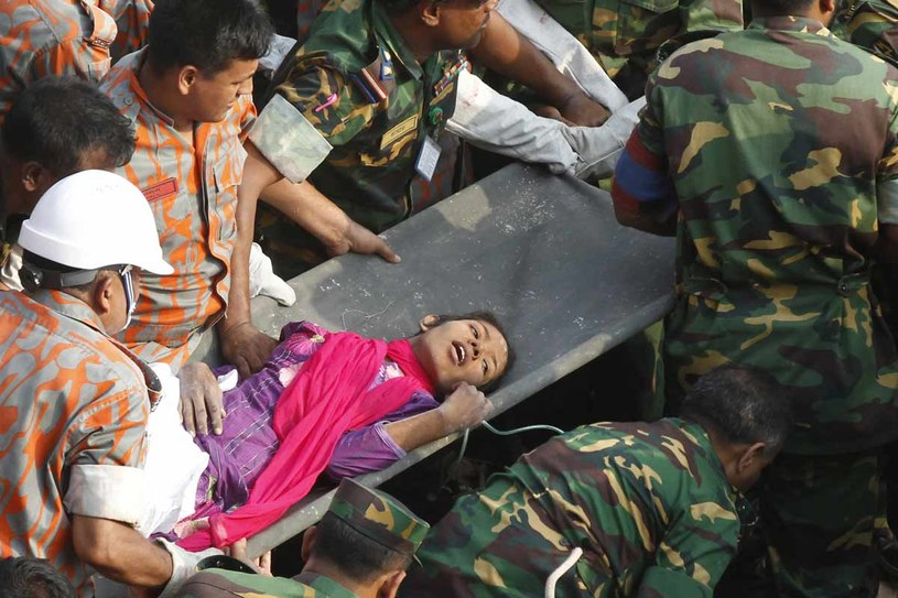 Bangladesz, rok 2013. Ratownicy wynoszą kobietę z gruzów fabryki odzieżowej, gdzie w wyniku zawalenia się budynku zginęło ponad 1000 osób /AFP