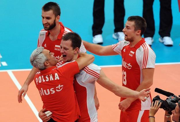 Bartosz Kurek w objęciach trenera Andrei Anastasiego, z lewej Marcin Możdonek,z prawej Michał Kubiak /AFP