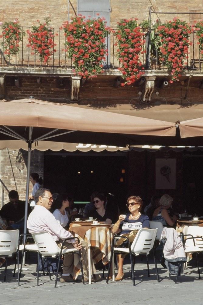 Będąc we Włoszech, usiądźmy przy kieliszku wina w knajpce na miejskim placu i, tak jak czynią to Włosi, poprzyglądamy się ludziom... /East News