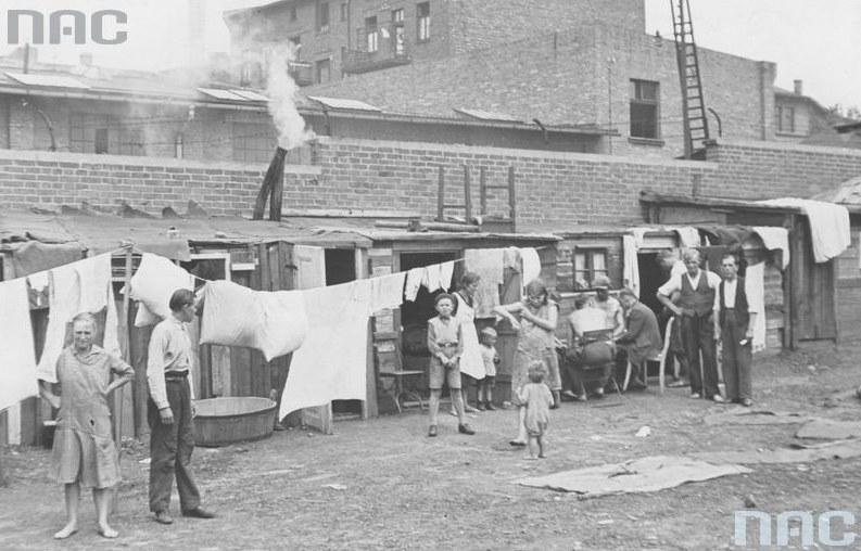 Bezrobotni mieszkańcy Królewskiej Huty przed swymi drewnianymi mieszkaniami /Z archiwum Narodowego Archiwum Cyfrowego