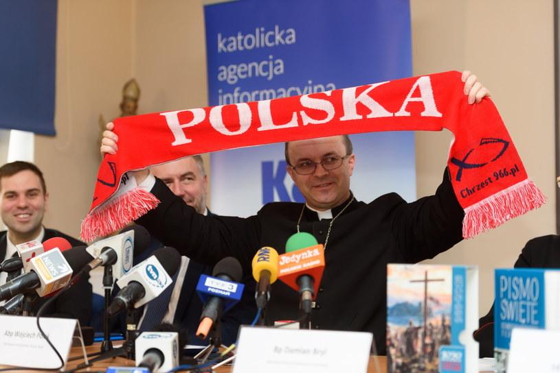 Biskup pomocniczy poznański ks. Damian Bryl prezentuje okolicznościowy szalik podczas konferencji prasowej poświęconej uroczystym obchodom 1050. rocznicy Chrztu Polski /Jakub Kaczmarczyk /PAP