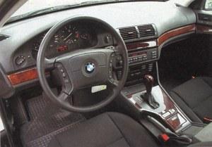 BMW serii 5 ma skromniejszy zestaw przyrządów i bogatsze drewnopodobne wykończenie. Kierownica wydaje się zbyt duża, a rozbudowana konsola wokół tunelu zabiera sporo miejsca. /Motor