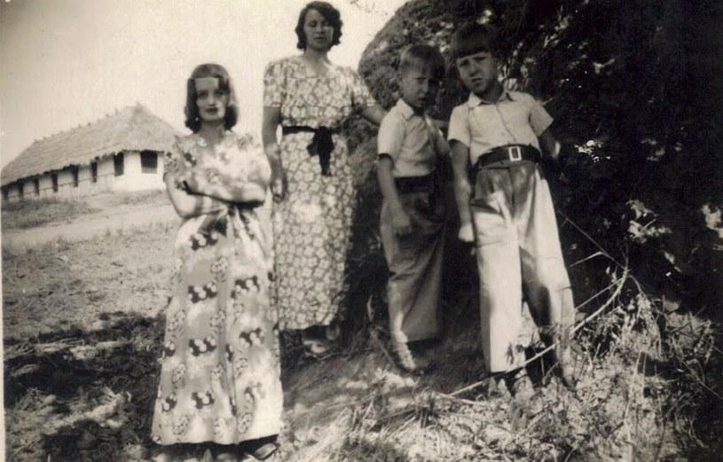 Bracia Woźniakowscy z mamą i znajomą pozują do zdjęcia obok termitiery przed ich domem. W tle magazyn, do którego chodziło się po żywność /Z archiwum Artura Woźniakowskiego /