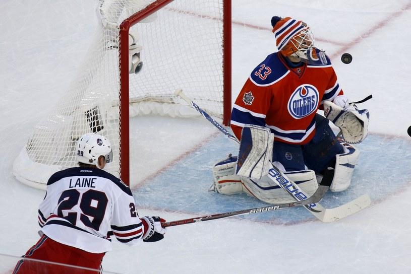 Cam Talbot z Edmonton Oliers broni strzał Patrika Laine'a z Winnipeg Jets /AFP