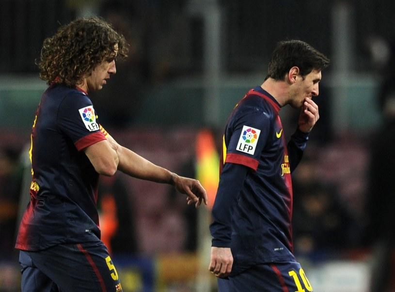 Carles Puyol i Lionel Messi schodzą z murawy Camp Nou po porażce z Realem 1-3 /AFP
