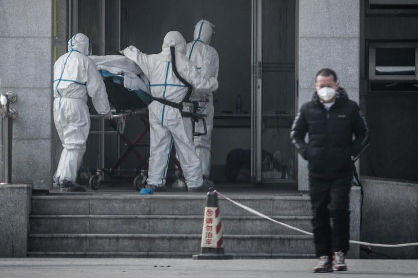 Chińskie służby medyczne transportują chorego z koronawirusem /AFP