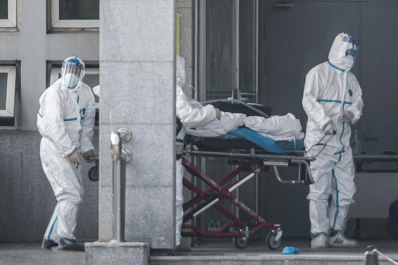 Chiny: personel medyczny transportuje pacjenta, u którego wykryto tajemniczy wirus /AFP