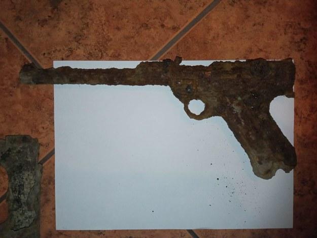 """Chłopcy przygotowując się do budowy """"bazy"""" znaleźli pistolet z okresu drugiej wojny światowej. Na miejsce wezwani zostali wolsztyńscy policjanci /KPP Wolsztyn /"""