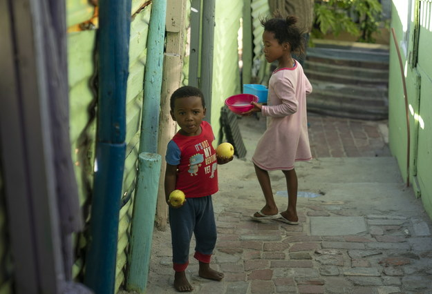Chłopiec i dziewczynka z Republiki Południowej Afryki po otrzymaniu jedzenia od lokalnej społeczności pomagającej najbardziej potrzebującym /SOUTH AFRICA PHOTO SET SHACK SETTLEMENT PANDEMIC COVID19 /PAP/EPA