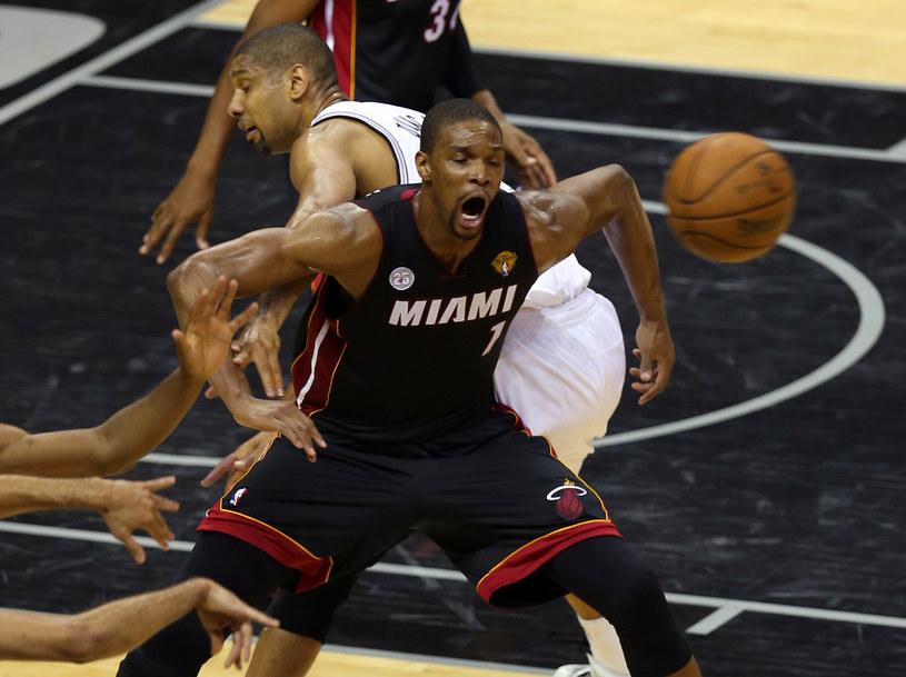 Chris Bosh z Miami Heat w walce o piłkę z Timem Duncanem z San Antonio Spurs /AFP