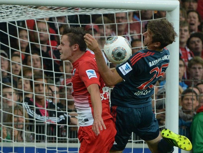 Christian Guenter (z lewej) w walce o piłkę z piłkarzem Bayernu Thomasem Muellerem /PAP/EPA