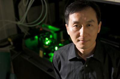 Chunlei Guo na tle lasera, który wykorzystuje do modyfikowania powierzchni  /University of Rochester