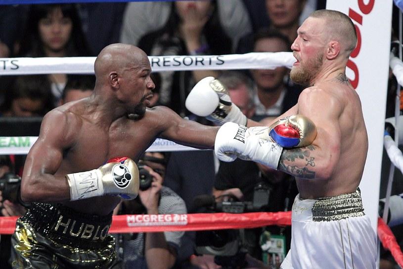 Conor McGregor (z prawej) w walce z Floydem Mayweatherem Jr. /JOHN GURZINSKI /AFP