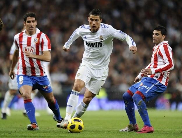 Cristiano Ronaldo (przy piłce), z lewej Raul Garcia, z prawej Jose Antonio Reyes /AFP