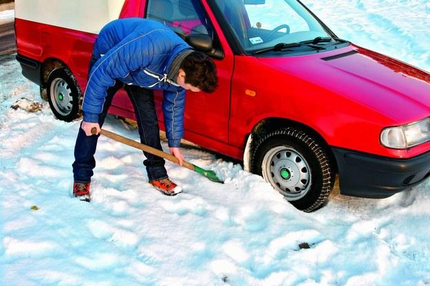 """Czasami koła stoją w dołkach i samochód nie ma siły podjechać. Usuńmy śnieg sprzed kół. Jeżeli samochód wisi """"na brzuchu"""" w głębokim śniegu, trzeba będzie usunąć śnieg. /Motor"""