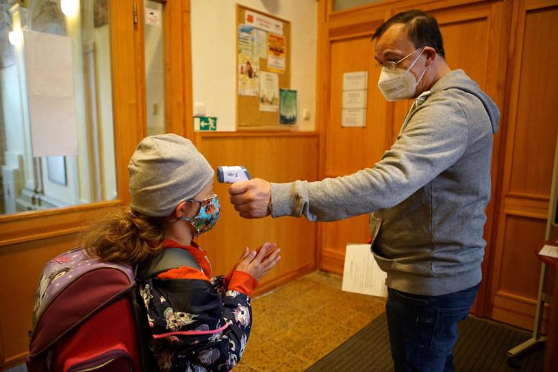 Czechy. Pracownik szkoły sprawdza, czy uczennica nie ma gorączki, zdjęcie ilustracyjne /Dana Kesnerova/Xinhua News/East News /East News