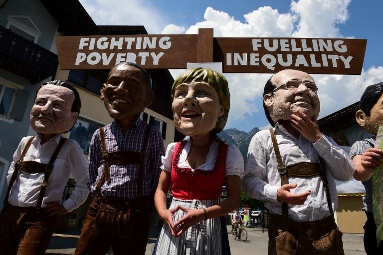 Członkowie organizacji Oxfam w tradycyjnych bawarskich strojach z maskami uczestników G7 /JOHN MACDOUGALL /AFP