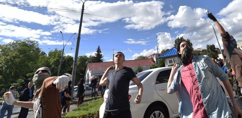 Demonstranci zablokowali wejścia do budynku oponami samochodowymi. Jeden z protestujących zerwał z masztu flagę Rosji /AFP