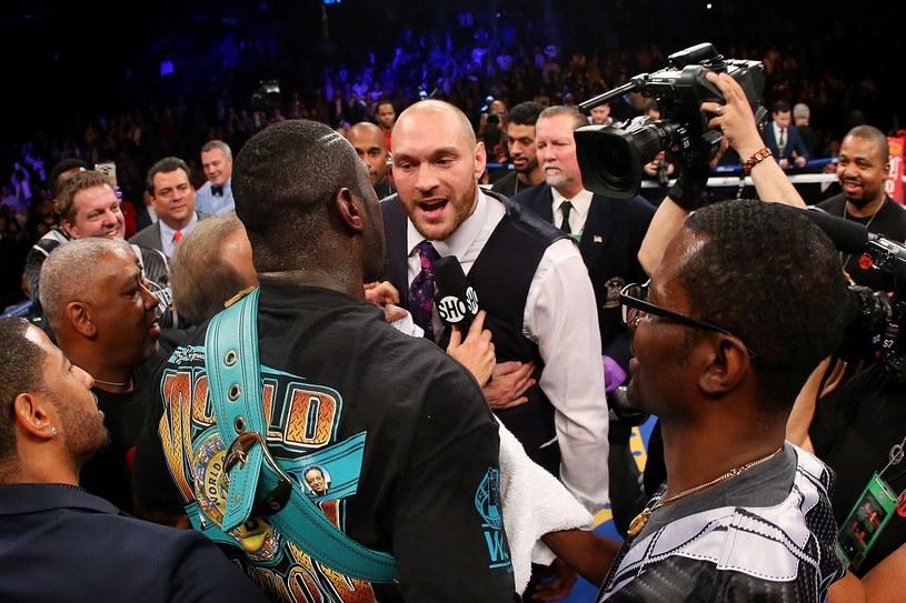 Deontay Wilder (odwrócony plecami) w rozmowie z Tysonem Fury'm /AFP