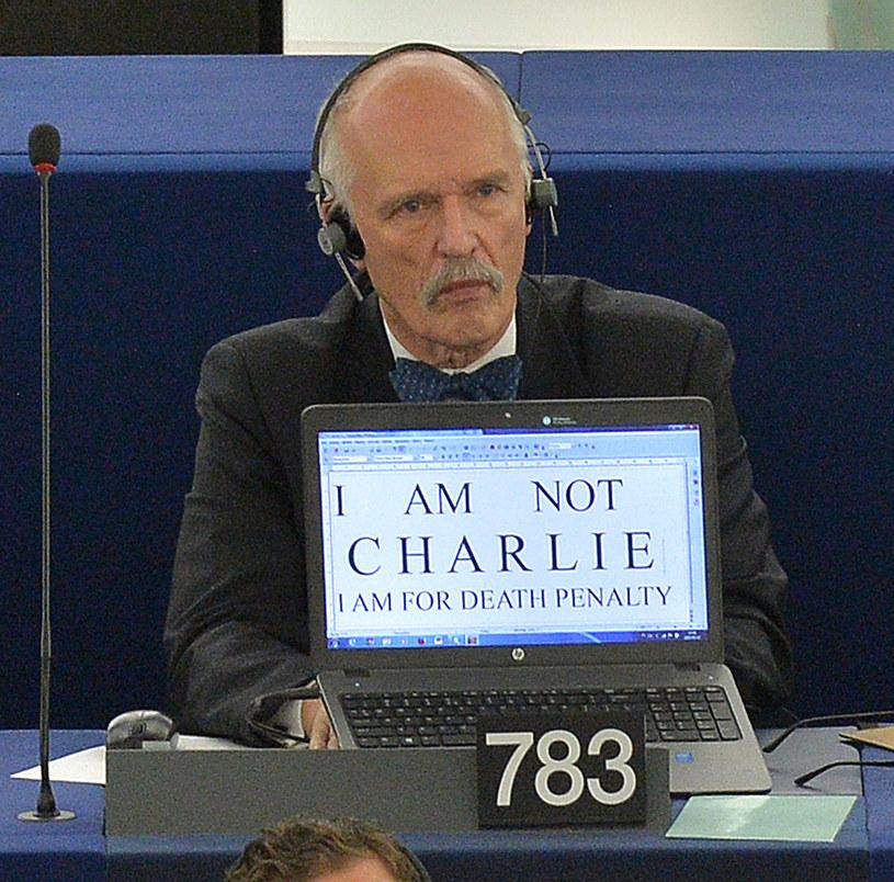 """Deputowani europarlamentu minutą ciszy i kartkami z napisem """"Jestem Charlie"""" uczcili ofiary paryskich zamachów. Janusz Korwin-Mikke zrobił to po swojemu. Na ekranie komputera napisał: """"Nie jest Charlie. Jestem za karą śmierci"""" /AFP"""