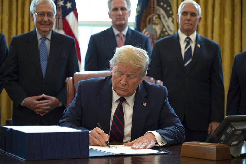 Donald Trump podpisuje ustawę; w tle zadowolony lider republikańskiej większość w Senacie Mitch McConnell (pierwszy z lewej) /AFP