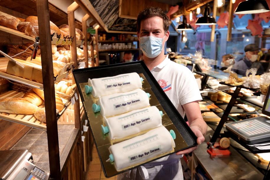 """Dortmundzki piekarz Tim Kortuem sprzedaje aromatyzowane marcepanem ciasta w kształcie strzykawki do szczepień, z pełnym nadziei napisem: """"2021 Bye Bye Corona"""". Cena rolady: 15 euro. /Friedemann Vogel /PAP/EPA"""