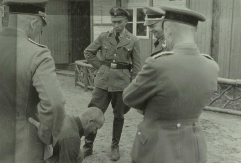 Dowództwo obozu znęcające się nad jednym z więźniów. Wśród oprawców znajduje się mąż Ilse Koch, Karl (drugi z prawej) /materiały prasowe
