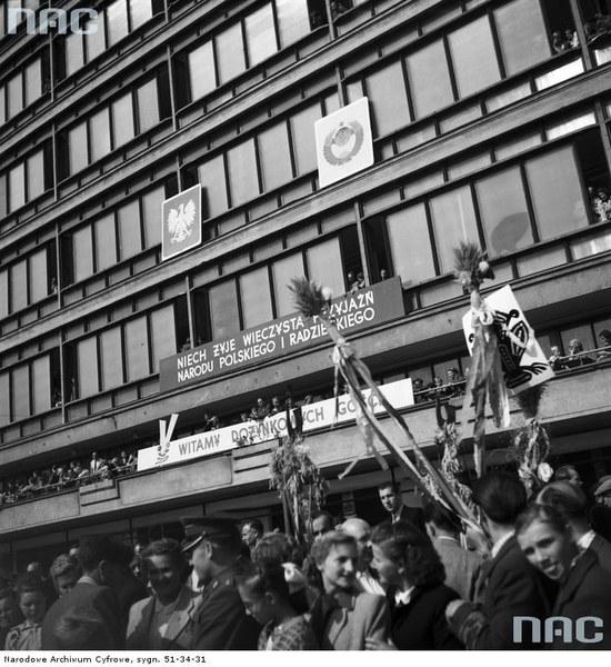 Centralne Dożynki w Warszawie, 1958. Obserwatorzy pochodu przy budynku Centralnego Domu Towarowego. Na elewacji widoczne hasła propagandowe