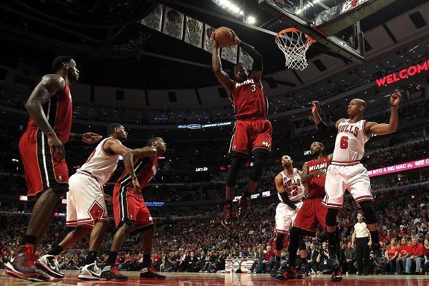 Dwyane Wade #3 z Miami Heat atakuje kosz Chicago Bulls, a Keith Bogans #6 go blokuje. /AFP