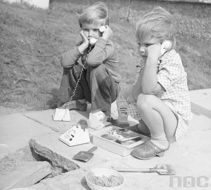 Dzieci podczas zabawy na chodniku przed blokiem. Widoczne zabawki - łopatki, telefony, kasa fiskalna i waga sklepowa. Fot Rutowska Grażyna, Narodowe Archiwum Cyfrowe/NAC /materiały prasowe