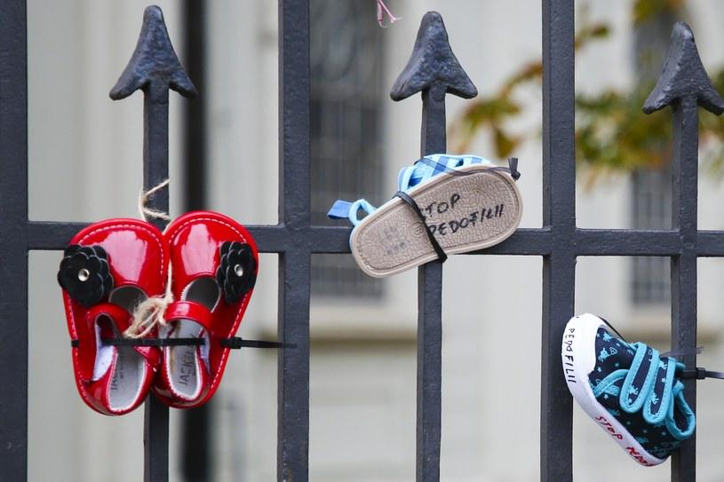 Dziecięce buciki zawieszone na ogrodzeniu kościoła w akcie sprzeciwu wobec wykorzystywania seksualnego małoletnich przez duchownych /Beata Zawrzel /East News