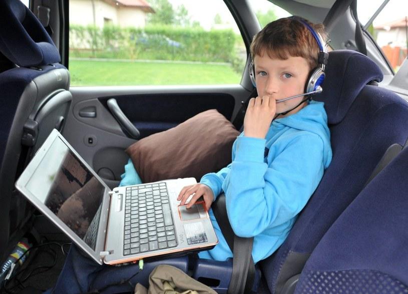 Dziecko spędza czas w podróży samochodem, grając na komputerze /PAP/Marcin Bielecki /PAP