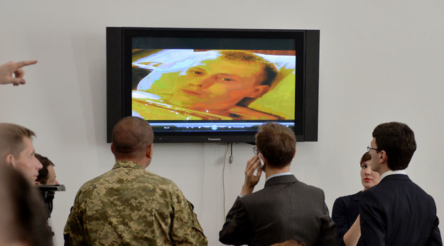 Dziennikarze i ukraińscy wojskowi oglądają wideo z ujętym rosyjskim żołnierzem fot. Genya Savilov /AFP