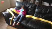 """Dziewczynka wypoczywa na kanapie z """"pupilem"""""""