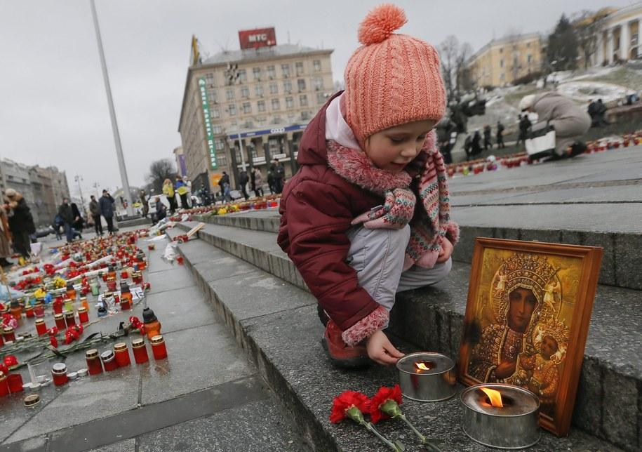 Dziewczynka zapala znicz w hołdzie ofiarom ostrzału Mariupola /SERGEY DOLZHENKO /PAP/EPA