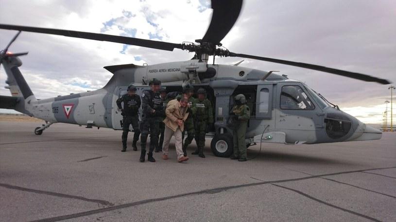 """""""El Chapo"""" (w jasnym kombinezonie) przed wylotem do USA /MEXICAN INTERIOR MINISTRY / AFP /AFP"""