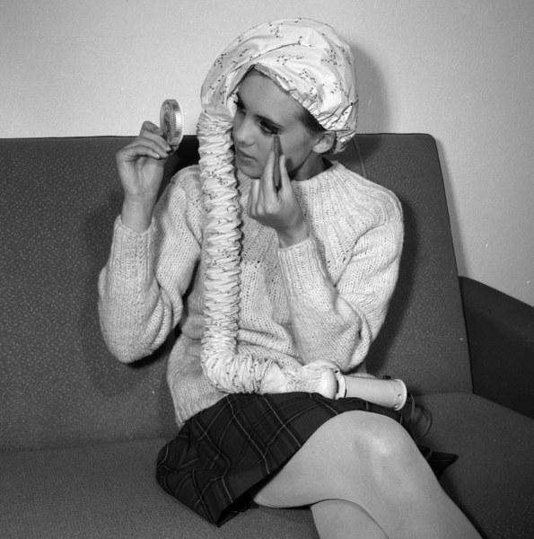 Warszawa, 1968, kobieta susząca włosy w czasie nakładania makijażu