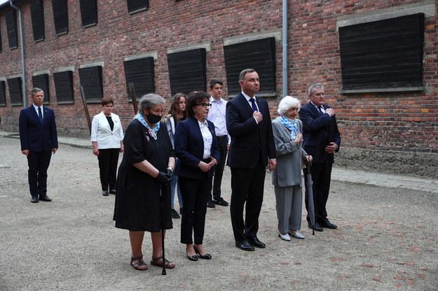 Europoseł PiS Beata Szydło (2L), wojewoda małopolski Piotr Ćwik (L), byłe więźniarki obozu Barbara Wojnarowska-Gautier (3L) i Lucyna Adamkiewicz (2P), wicepremier, minister kultury i dziedzictwa narodowego Piotr Gliński (P), prezydent Andrzej Duda (3P) oraz marszałek Sejmu Elżbieta Witek (4L) składają wieńce pod Ścianą Straceń na dziedzińcu bloku 11 w byłym obozie Auschwitz I