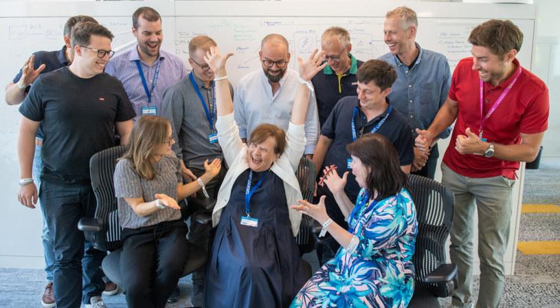 Felicitas Hanne z radością podnosi ręce, otoczona przez niektórych członków zespołu Microsoft Germany, który opracował rozwiązania dla Kinderhaus AtemReich. Zdjęcie: Microsoft /materiały prasowe
