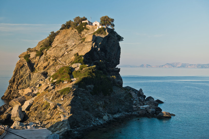 """Filmowy duet dawnych narzeczonych Meryl Streep i Pierce Brosnan śpiewa wielki przebój ABBY """"The Winner Takes It All"""" na skalistym półwyspie z cerkwią Agios Ioannis na szczycie. To romantyczne miejsce na wschodnim wybrzeżu Skopelos jest najbardziej popularnym celem wycieczek po wyspie"""
