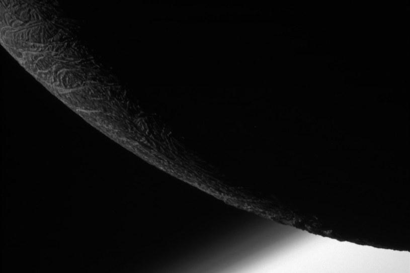 Fragment krawędzi Enceladusa z atmosferą Saturna w tle /NASA